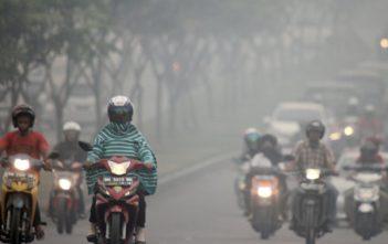 Penggendara melintasi jalan yang dipenuhi kabut asap sisa kebakaran hutan dan lahan di Jalan Soekarno Hatta, Pekanbaru, Riau, Selasa (18/2). Tebalnya kabut asap membuat pengguna jalan raya harus lebih ekstra berhati-hati karena terbatasnya jarak pandang. ANTARA FOTO/Rony Muharrman/ed/pd/14