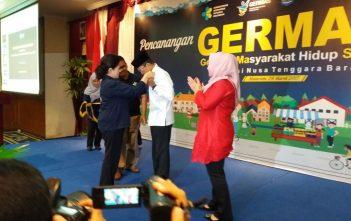 Menteri Kesehatan RI Prof. Nila Moeloek, SpM (K) menyematkan pin duta ASI kepada Gubernur NTB Tuan Guru Haji Zaenul Bajebi (Kemeja putih), di Mataram, Nusa Tenggara Barat (29/3). Hal ini dilakukan karena Provinsi NTB adalah salah satu provinsi dengan cakupan ASI eklusif tertinggi di Indonesia.